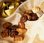 Various chocolates, fine fabric, gold ribbon behind