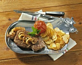 Rump steak with onions, fried potatoes & tomatoes on plate