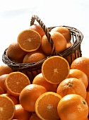 Oranges, whole and halved, in front of and in a basket