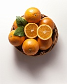Whole oranges & two halves with leaves in basketwork bowl