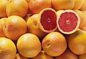 Pink grapefruits with two grapefruit halves (close-up)