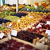 Lots of different fruits in crates on a market stall
