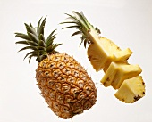 Whole pineapple and a pineapple quarter, a slice cut