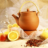 Terracotta tea pot, beside it fruit tea, lemons and apples