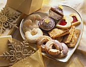 Various Christmas biscuits on heart-shaped plate