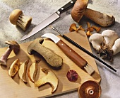 Mushroom slices on wooden board with knives & cleaning tool