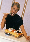Young blond woman eating sushi with chopsticks