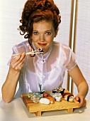 Rothaarige Frau isst Sushi mit Stäbchen vom Holzbänkchen