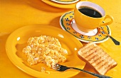 Scrambled egg, slice of toast and a cup of coffee