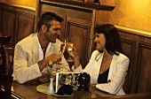 Man and woman in restaurant clinking champagne glasses