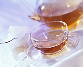 Tea in glass cup and teapot; white crystal sugar