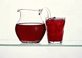 Cherry juice in glass jug & in glass with ice cubes