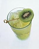 A glass of kiwi juice with ice cubes, garnished with kiwi slice