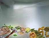 Arrangement with pasta, ravioli, pasta dough & pastry wheel