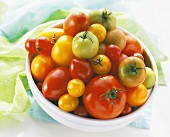 Various types of tomatoes in dish on green cloth
