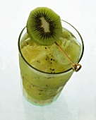 Kiwi juice with ice cubes in glass with kiwi slice garnish