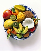 Exotic fruits with halved coconut on plate