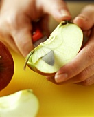 An apple being cored, on yellow chopping board