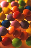 Colourful chocolate beans (Smarties) on yellow background