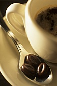 Coffee-bean-shaped chocolate beans on spoon beside coffee cup