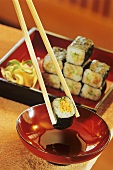 Chopstick with an umekyo natto maki above red bowl