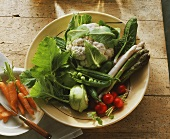 Various spring vegetables in a bowl, carrots beside it