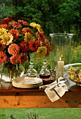Buffet table with crockery, salad and flowers in open air
