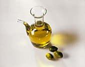 Carafe of olive oil and three green olives