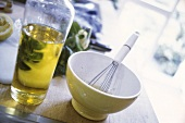 Marinade in bowl & bottle of olive oil on kitchen table