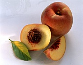 Whole and half peach, peach slice and leaf