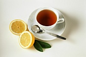 A cup of tea, sliced lemon beside it