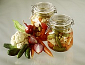 Two jars of Mixed Pickles, fresh vegetables beside them