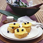 Three pieces of pineapple cake with mango slices & blueberries