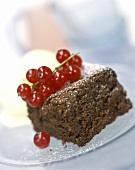 A piece of chocolate cake garnished with redcurrants