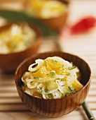 Onion & celery salad with orange pieces in wooden bowl