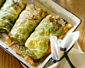 Several cabbage parcels in a roasting dish