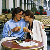 Young couple at café table with orange juice, champagne, olives