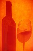Schatten von Rotweinglas und -flasche auf oranger Fläche