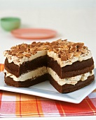 Chocolate cream gateau with flaked almonds, a piece cut