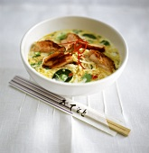 Coconut milk curry with noodles, salmon and lemon leaves