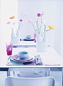 Pastel-coloured table setting  and vases of flowers on table