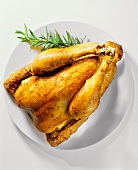 Roast capon (large chicken) with rosemary on plate