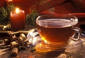 Spiced Christmas tea in glass cup; spices; candle