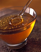 Honey with a glass spoon in glass bowl