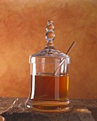 Honey with glass spoon in decorative jar
