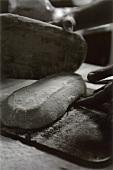 Brotteig wird aus der Form aufs Blech gebracht (s-w-Aufnahme)