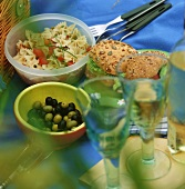 Picnic with pasta salad, olives, rolls and wine