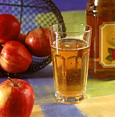 A glass of apple drink, bottle and fresh apples beside it
