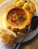 Pumpkin seed soup with tomatoes in hollowed-out pumpkin