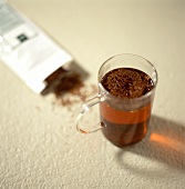 Rooibos tea in packet and brewed in glass